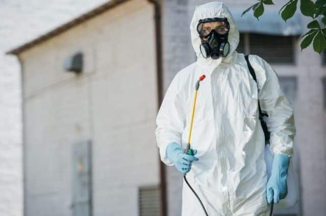 pest exterminator in white protective suit